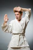 Funny karate fighter wearing white kimono — Stock Photo