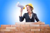 Woman builder and brick wall — Stockfoto