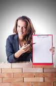 Woman builder and brick wall — Stock Photo