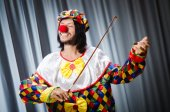 Grappige clown plyaing viool tegen gordijn — Stockfoto