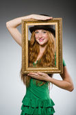 Woman wearing green dress holding picture frame — Stock Photo