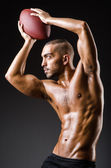Muscular football player with ball — Stockfoto