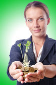Businesswoman with seedlings and coins — Stock Photo
