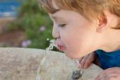 Toddler drinking from the water fountain — Stock Photo