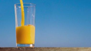 Pouring a glass of orange juice creating splash — Stock Video