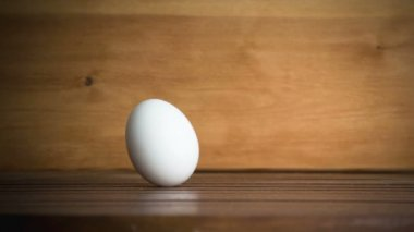 An egg is rolling across the table. Slow motion — Stock video