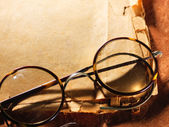 Vintage glasses on old paper — Stock Photo
