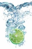 Lime dropped into water — Stock Photo