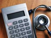 Calculator and stethoscope on background — Stockfoto
