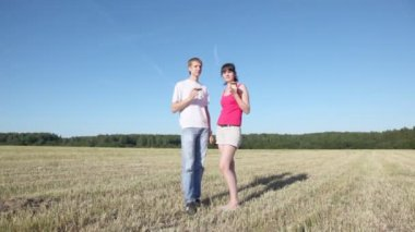 Guy with girl stand in field — Stock Video