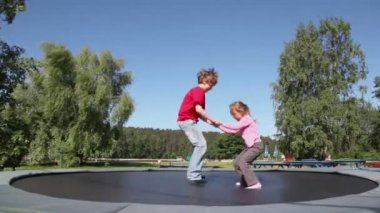 Boy with girl jump on trampoline — Stock Video