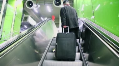 Man with trunk lifts on escalator — Stock Video