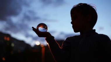 Boy holds transparent glass sphere — Stock Video
