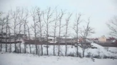 Cottages at village on winter day, view from train — Stock Video