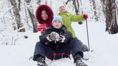 Mother sings on sled with children — Stock Video