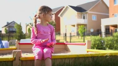 Little girl sits and plays with sand — Stock Video