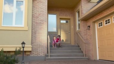 Two kids sit at porch — Stock Video