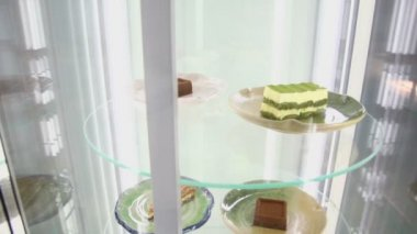 Cakes on plates spin in glass showcase — Stockvideo