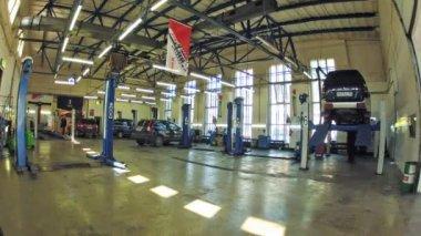Mechanic repairs car bottom in car-care center — Stock Video
