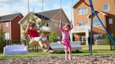 Boy and girl sway on swings — Stock Video