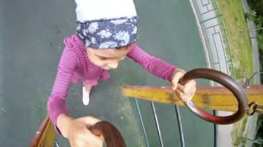 Little girl hangs on sports rings — Stockvideo