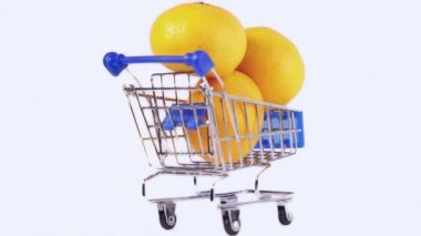 Three oranges in miniature shopping cart — Stock Video