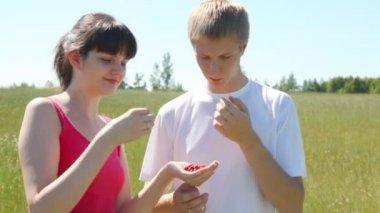 Ragazza e ragazzo mangia la fragola selvatica — Video Stock