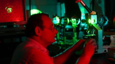 Scientist adjusting microscope — Stockvideo