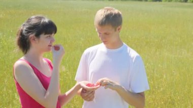 Girl and guy eat wild strawberry — Stock Video