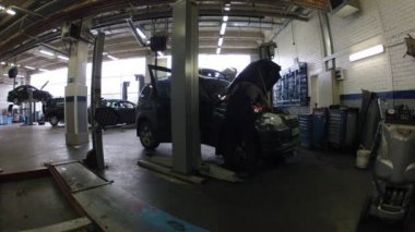 Car stands with lifted cowl in car-care center — Stock Video