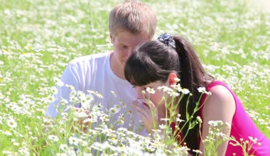 Young couple in camomile field — Stock Video