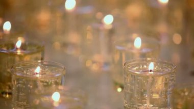 Many candles burn in glasses — Vídeo de stock