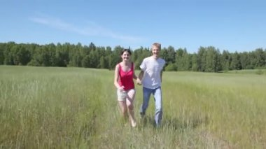 Guy with girl run in field — Stock Video