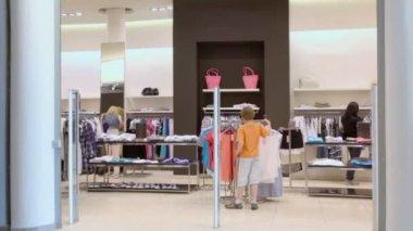 Little boy walks in womens clothes shop — Stock Video