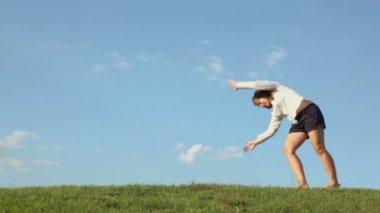 Girl rolls on grass hill — Stock Video