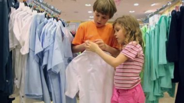 Two kids in clothes shop — Stockvideo