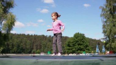 Little girl jumps on trampoline — Stok video