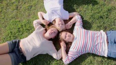 Three girls lay on grass — Stock Video