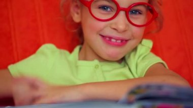 Little girl in red glasses sits — Stock Video