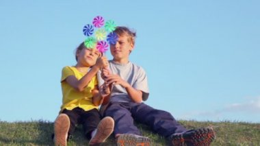 Two kids play with windmill toy — Stock Video