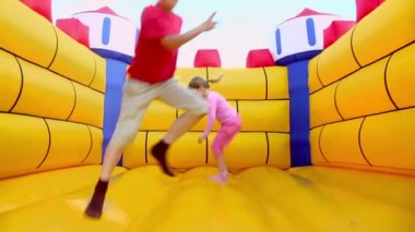 Boy and girl at inflatable playground — Stock Video