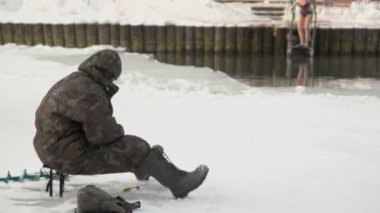 Fisherman sits near ice hole — Stock Video