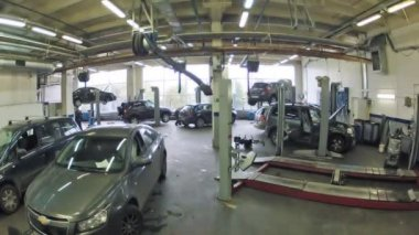 Cars are fixed on lifting-jack hoist in garage — Stock Video