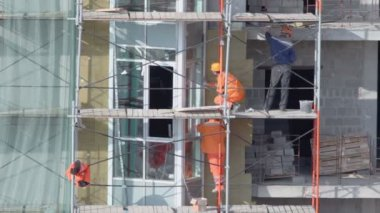 Workers stand on scaffold and set windows — Stock Video