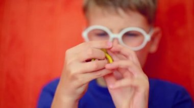 Young boy twists flexible pencil — Stock Video