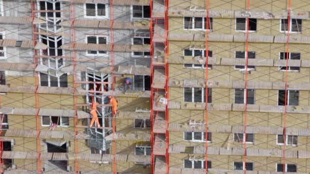 Workers in orange uniform on scaffold — Vidéo