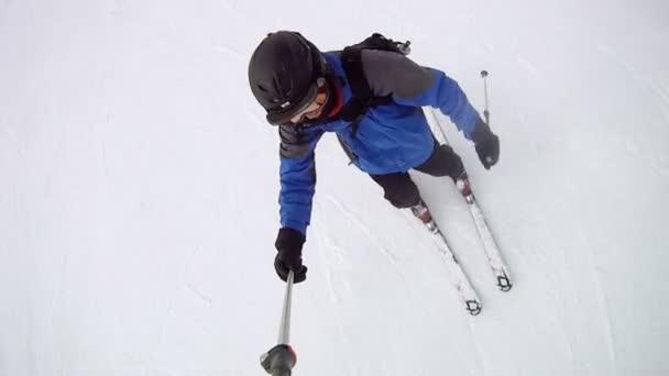 Esquiador desciende en cuesta de la montaña — Vídeo de stock