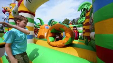 Children jump at inflatable playground — Stock Video