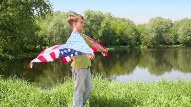 Boy holds unfolded US flag — Stock Video
