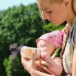 Young mother feeds her baby — Stock Video #65075645